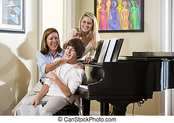 Family sitting on piano bench, mother teasing son