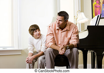 Father with teenage son sitting together at home