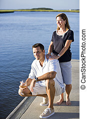 Couple relaxing with drink on dock by water