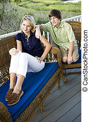 Teenage girl and brother sitting on terrace