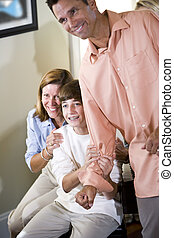 Teenage boy and parents at home looking excited
