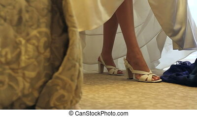Bride Dresses wedding shoes with the help of friend in the...