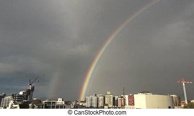 Rainbow above city skyline urban cityscape.