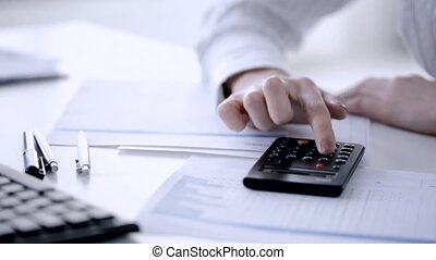 female accountant making fast calculations - closeup of...