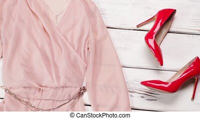 Glossy footwear and salmon dress. Woman's luxury clothing on...