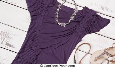 Dark purple dress and sandals. Dark garment on white shelf....