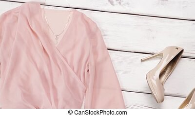 Dress and silver clutch bag. Light salmon dress on table....