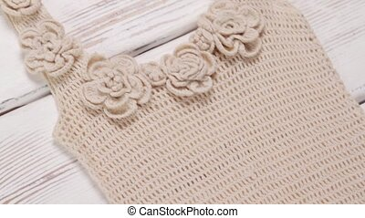 Lady's beige knitted tank top. Knitted handmade garment on...