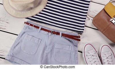 Light shorts with striped top. Girl's summer outfit on...