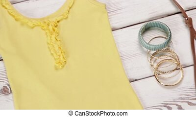 Yellow top and flip-flops. Bright-colored garments on...