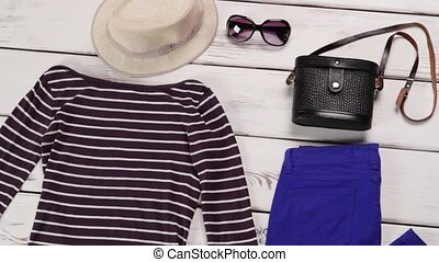 Striped top and blue pants. Woman's spring outfit on table....