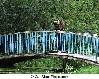 young woman on the bridge - young woman on a bridge over the...