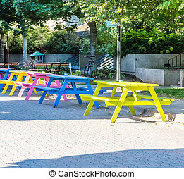 Colorful Picnic Tables on Cobblestone Street - A line of...