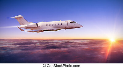 Private jet plane flying above clouds in sunset