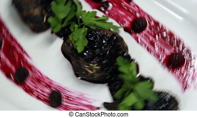 meat was put on the white plate and decorated with currant's sause and parsley