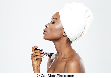 Afro american woman applying makeup with brush - Side view...