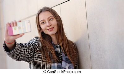 Young attractive woman wearing casual black and white coat is taking selfies by her mobile phone on the street.