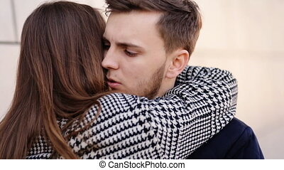 Beautiful happy woman tenderly hugging her boyfriend and...