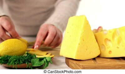 A woman prepares a snack of cheese with white wine.