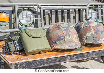 Helmet military and Military flask on wooden table.