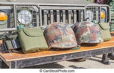 Helmet military and Military flask on wooden table