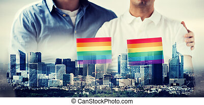 close up of male gay couple holding rainbow flags - people,...