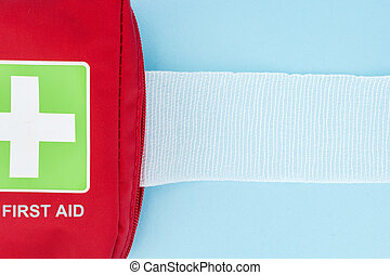 Red first aid kit with unrolled gauze, on light blue...