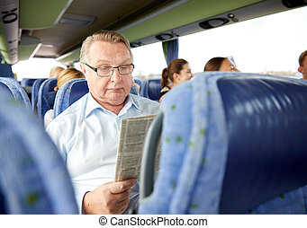 happy senior man reading newspaper in travel bus -...