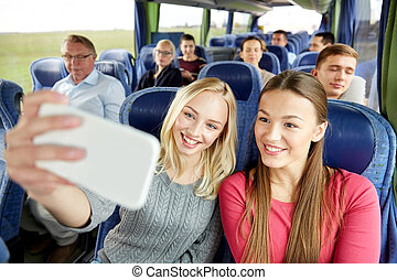 women taking selfie by smartphone in travel bus - transport,...