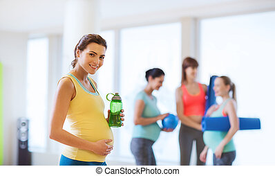 happy pregnant woman with water bottle in gym - pregnancy,...