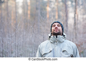 Man breathing deeply in peaceful winter forest on cold day