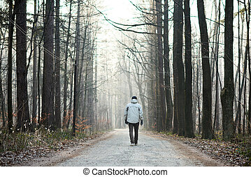 Man walking away down road between trees in winter forest -...