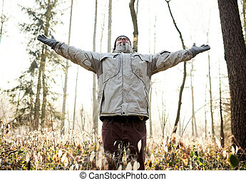 Man breathing in the fresh air of a winter forest