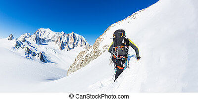 Mountaineer climbs a snowy peak. In background the glaciers and the summit of Mont Blanc, the highest european mountain.