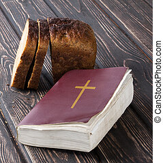 Bible and bread on a wooden board