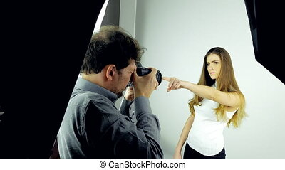 Backstage of photo session in studio with female model and photographer dolly shot 4K