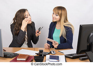 Office workers talking animatedly about cosmetics at your...