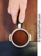 Hand holding perfectly even ground coffee in shiny portafilter