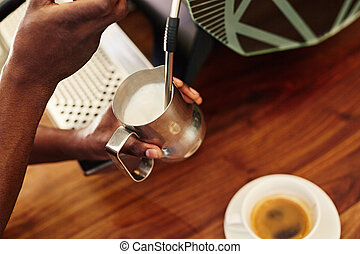 Barista steaming milk in stainless steel jug at espresso machine