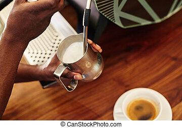 Barista steaming milk in stainless steel jug at espresso machine