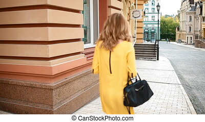 Young woman walking down the street - Young woman in yellow...