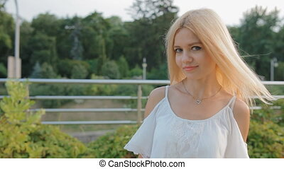 Young blonde woman in light white dress outdoors - Young...