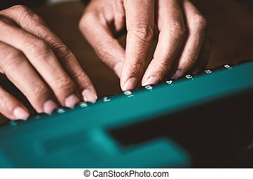 man typing in a retro blue typewriter - closeup of the hands...