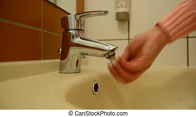 woman washes her hands in bathroom - A woman washes her...