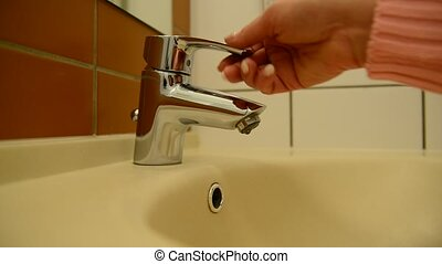 Female hand opens water tap and try water temperature -...