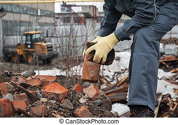 blockages of broken bricks - worker takes down blockages of...