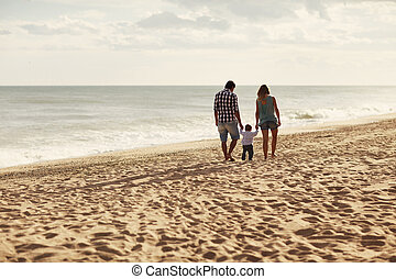 Family walking on the beach - Couple and their toddler...