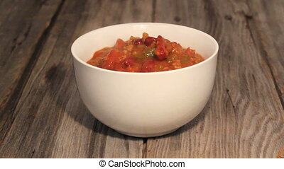 pouring chili con carne in a bowl