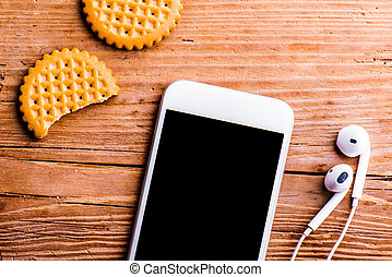 Smartphone, earphones and biscuits laid on old office desk -...