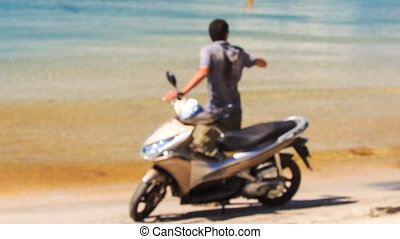Closeup Backside Guy Stands by Motorbike Lifts Hand on Beach...